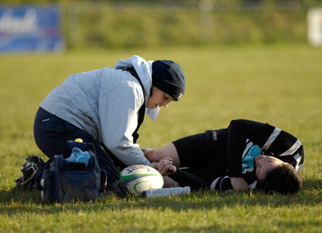 Image of doctor treating rugby player on field. Credit: Alamy
