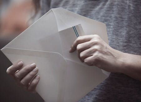 Picture of someone opening letter. Credit: Plainpicture