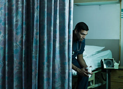 Hospital doctor sitting behind curtain