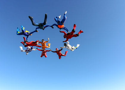 Group of skydivers holding hands together