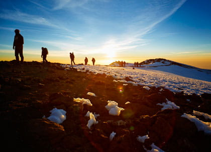 Group of mountain climbers at sunrise